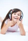 Girl is enjoying music using headphones Stock Photo