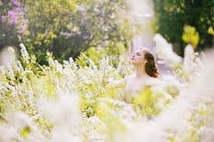 Girl enjoying nature. Beautiful girl in a big spirea bush, girl enjoying nature Stock Photography