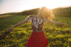 Girl enjoying nature on the field . The girl is joyful spinning with a wreath of flowers in her hands royalty free stock photo
