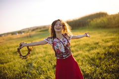 Girl enjoying nature on the field . The girl is joyful spinning with a wreath of flowers in her hands stock image