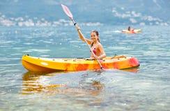 Girl enjoying paddling in kayak on the sea water Stock Photography