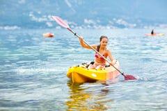 Girl enjoying paddling in kayak on the sea water Royalty Free Stock Photos