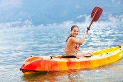 Girl enjoying paddling in kayak on the sea water Stock Photos