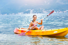 Girl enjoying paddling in kayak on the sea water Stock Photo
