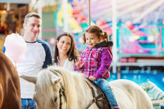 Girl enjoying pony ride, fun fair, parents watching her. Little girl enjoying a ride on pony at fun fair, parents watching her, amusement park Royalty Free Stock Photo