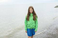 Girl enjoying the rain and having fun outside on the beach  a gray rainy Stock Photography