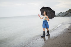 Girl enjoying the rain and having fun outside on the beach  a gray rainy Royalty Free Stock Images