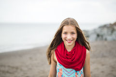 Girl enjoying the rain and having fun outside on the beach  a gray rainy Royalty Free Stock Image