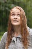 Girl enjoying rain in the park. stock photos