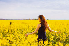 Girl enjoying rapeseed blooming on yellow meadow Royalty Free Stock Image