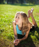 Girl enjoying relaxation lying in the green grass Royalty Free Stock Photo