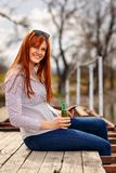 Girl enjoying and relaxing out in nature and drinking beer by th stock photography