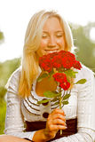 Girl enjoying the scent of red roses. Girl enjoying the scent of flowers outdoors stock photos