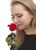 Girl enjoying the scent of a single red rose Royalty Free Stock Photos