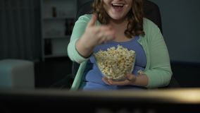 Girl enjoying silly program on TV at home, eating and scattering popcorn around. Stock footage stock footage