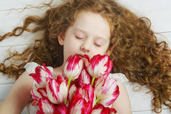 Girl enjoying the smell of tulips closed her eyes. Stock Images