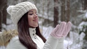 A girl is enjoying a snowfall in the winter forest. Beautiful girl with long dark hair in a white jacket walking in a winter fores stock video footage