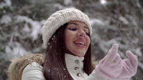 A girl is enjoying a snowfall in the winter forest. Beautiful girl with long dark hair in a white jacket walking in a winter fores stock video