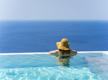 Girl Enjoying Summer in Pool. Back portrait of a girl with large hat enjoying the sea and summer vacation in a pool Stock Photo