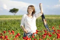 Girl enjoying summer in a poppy field Stock Photo