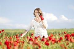 Girl enjoying summer in a poppy field Stock Images