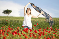 Girl enjoying summer in a poppy field Stock Photography