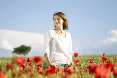 Girl enjoying summer in a poppy field Stock Photos