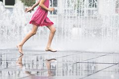 Girl enjoying summer running freely through fountain water Stock Photography