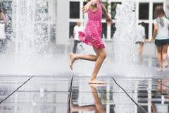 Girl enjoying summer running freely through fountain water. In city Stock Photos