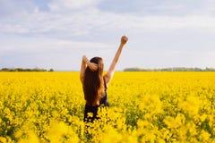 Girl enjoying sun on rapeseed meadow Stock Photo