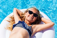 Girl enjoying suntan on mattress in swimming pool. Top view portrait of preteen blond girl in bikini and sunglasses, enjoying suntan on inflatable mattress in Stock Photography