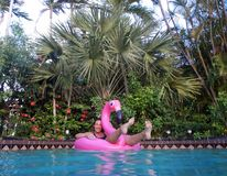 Girl enjoying in the swimming pool on flamingo float. Girl enjoying in the swimming pool on pink flamingo float in yard full of palms Royalty Free Stock Images