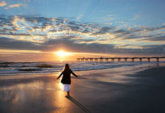 Girl enjoying time on the beach at sunrise. Stock Images