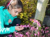 Girl Enjoying Time In Garden Observing Flowers Stock Images