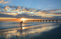 Girl enjoying time walking on the beautiful beach at sunrise. Stock Photo