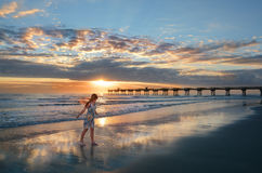 Girl enjoying time walking on the beautiful beach at sunrise. Royalty Free Stock Photos