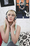 Girl Enjoying To Music Through Headphones In Bed Stock Image