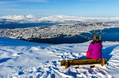 Girl enjoying view of Tromso from Fjellstua. A girl sitting on a bench enjoying panoramic winter view of Tromso Island, Norway, from the upper station of the Royalty Free Stock Photography