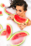 Girl enjoys a bath with milk and watermelon. Stock Photos