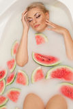 Girl enjoys a bath with milk and watermelon. Stock Photo