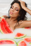 Girl enjoys a bath with milk and watermelon. Stock Image