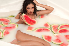 Girl enjoys a bath with milk and watermelon. stock image