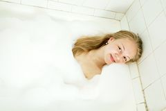 Girl enjoys in the bathtub Royalty Free Stock Photos