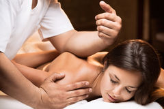 The girl enjoys deep tissue massage. The beautiful young girl enjoys deep tissue massage with professional masseur Royalty Free Stock Image