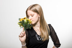 A girl enjoys flowers. A blonde girl enjoys a bouquet of yellow flowers Royalty Free Stock Image