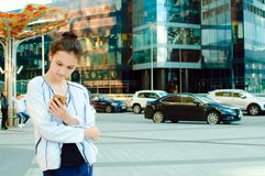 A girl enjoys the Internet with a mobile phone in the background of a business center build stock images