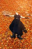 Girl enjoys the last sunbeams in orange autumn. Teenage girl dressed in gothic style enjoys the last sun in autumn forest. She lies on the orange foliage