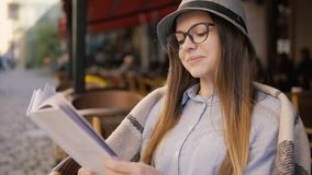 Girl Enjoys Leisure Time. Beautiful girl, in a grey striped hat, enjoys leisure time with pleasant book and cup of hot coffee, outdoor slowmotion stock video footage