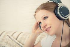 Girl enjoys listening to music on headphones. Beautiful girl enjoys listening to music on headphones while lying on the sofa Stock Photo