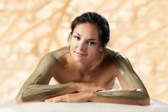 The girl enjoys mud body mask in a spa salon. Royalty Free Stock Photos